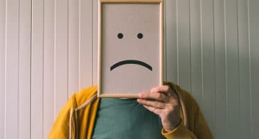 depressed man holding a picture of a sad emoticon over his face